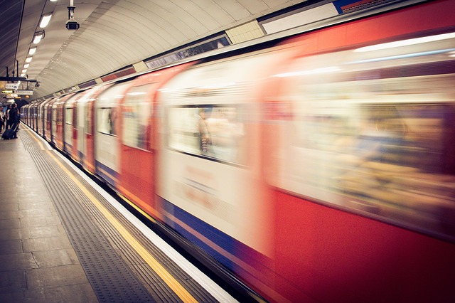 A blurry London Underground train departing/arriving from a platform.