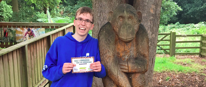 Young man in blue jumper holding a certificate next to a monkey statue