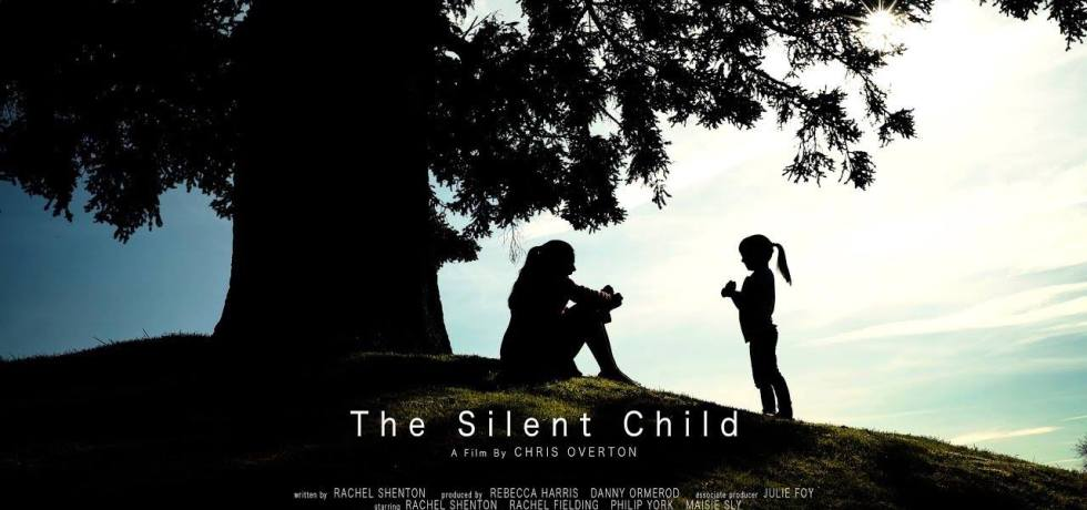 The Silent Child Film Poster, showing silhouettes of a tree on a hill, a woman sitting down and a young girl with a ponytail standing facing her.