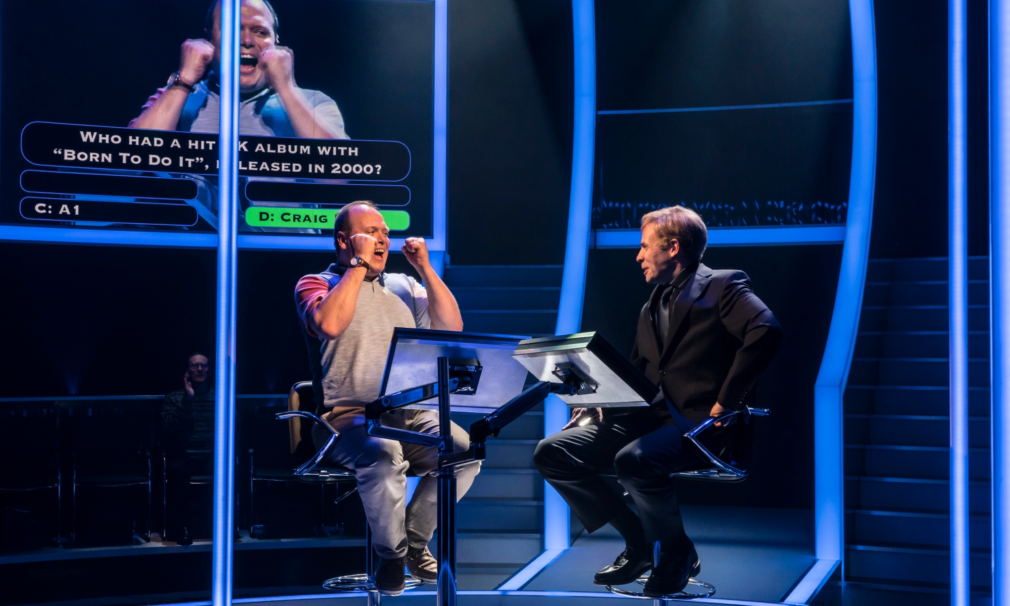 Production image of Quiz showing a contestant on the left raising his fists as he got a correct answer, while the actor on the right playing Chris Tarrant smiles.