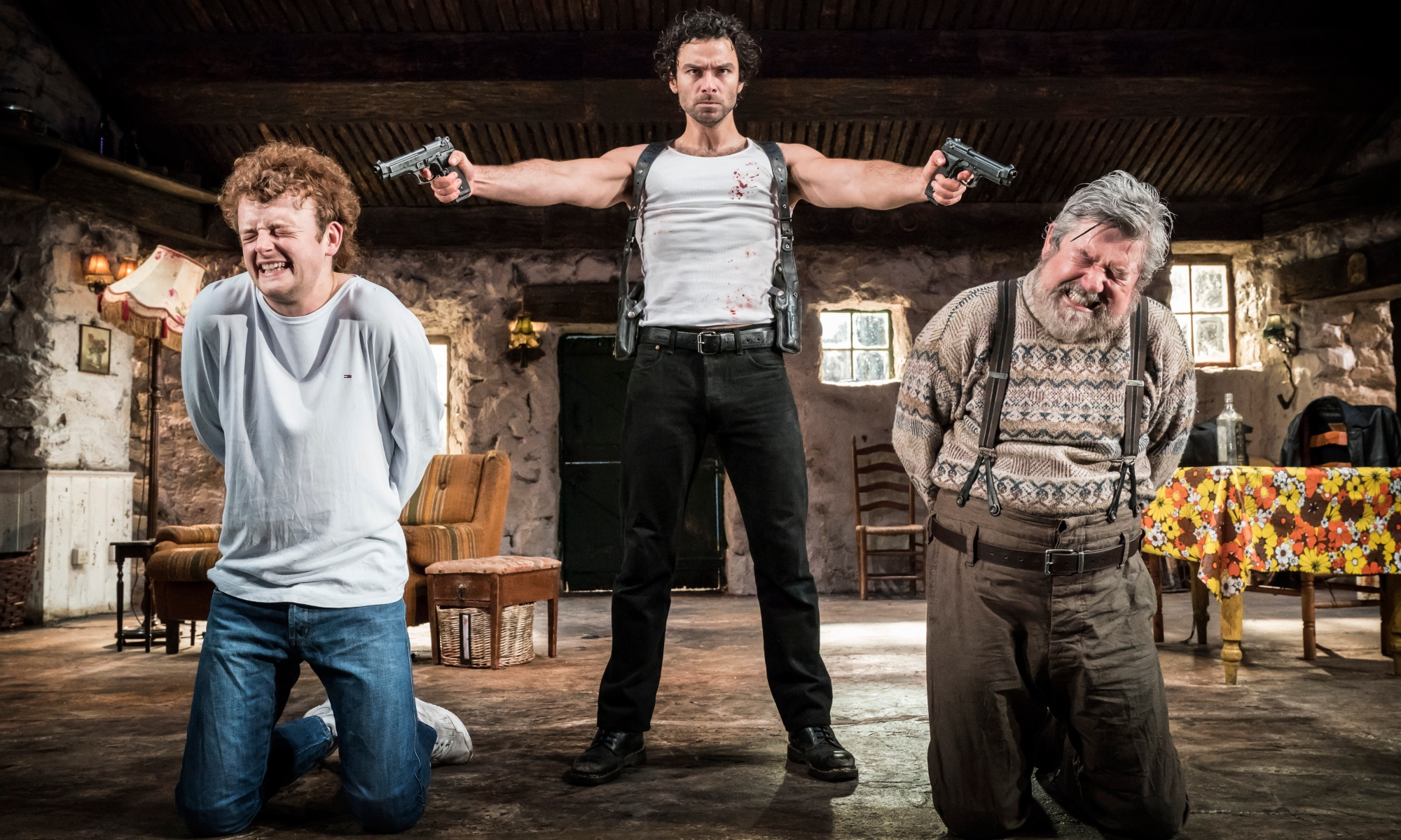 Two men are kneeling, eyes closed, wincing in fear with hands behind their back. In the centre, Aidan Turner has a serious expression and is pointing pistols at both of their heads.