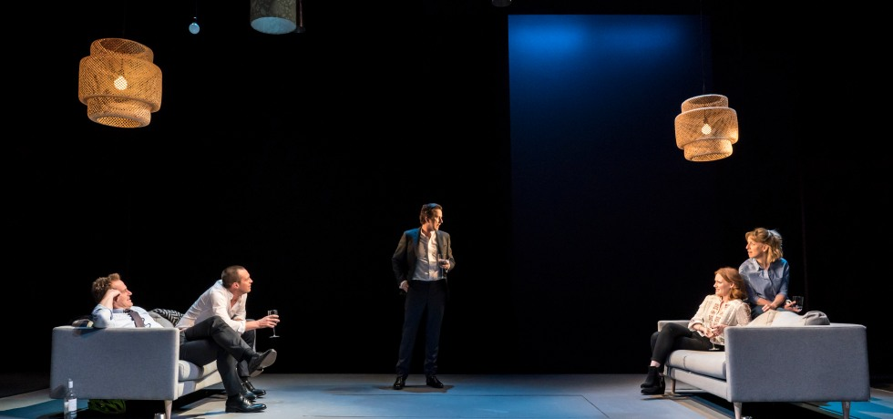 Two sofas are on stage on the far left and far right. Two actors are sitting on each. In the middle is a male who is looking at someone on the right sofa.