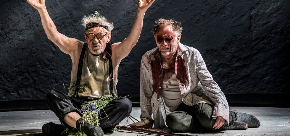 Ian McKellen (left) and Danny Webb (right) sit on the floor. Ian as Lear is wearing a green vest, is wearing glasses and has flowers in his lap. Danny as Gloucester is wearing a bloodstained shirt, has blood around his eyes (to suggest they are no longer there) and has a cane on the floor in front of him.