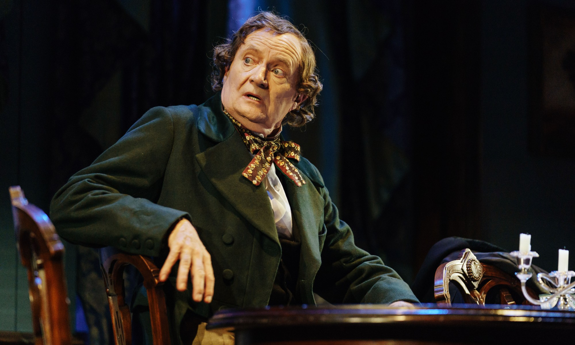 Jim Broadbent as Hans Christian Andersen, in a green coat sitting at a wooden table.
