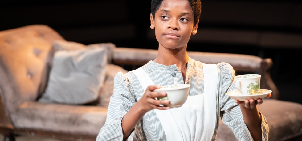 Letitia Wright wearing a white dress, holding two cups of tea. A chaise longue is behind her in the background.