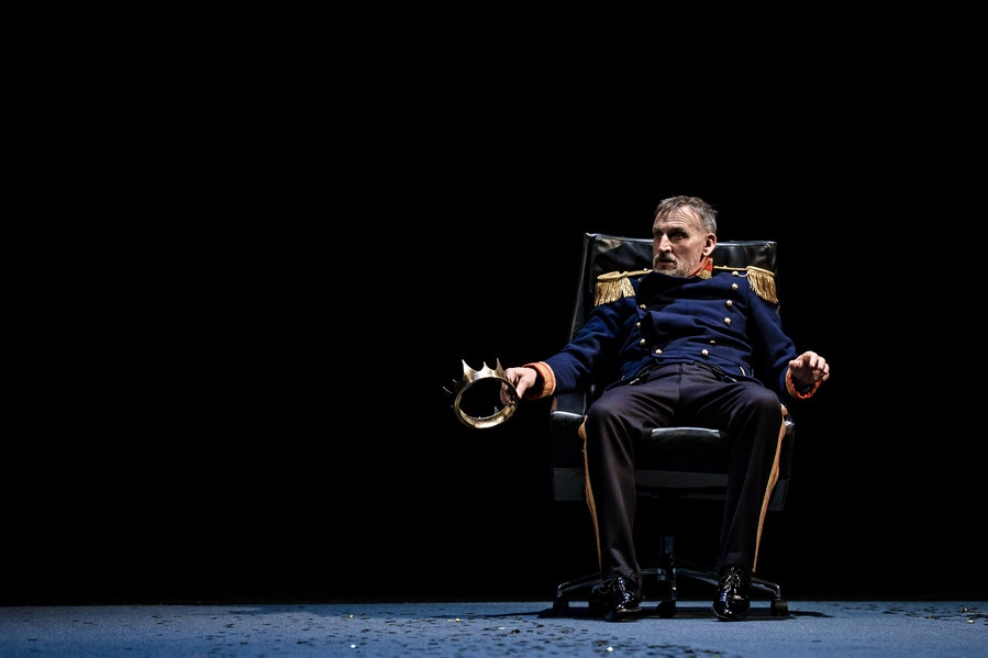 Christopher Eccleston as Macbeth, wearing blue royal wear, sitting in a black swivel chair and holding a crown in his right hand.