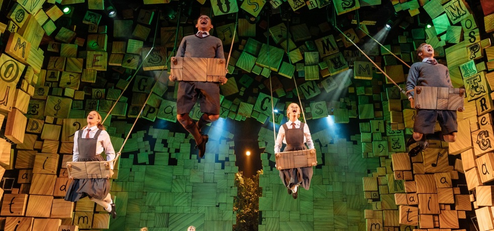 Production image for Matilda, showing four people on giant swings in the air, a series of books and letters, sprawled over the ceiling of the stage, and four younger actresses standing and singing on stage.