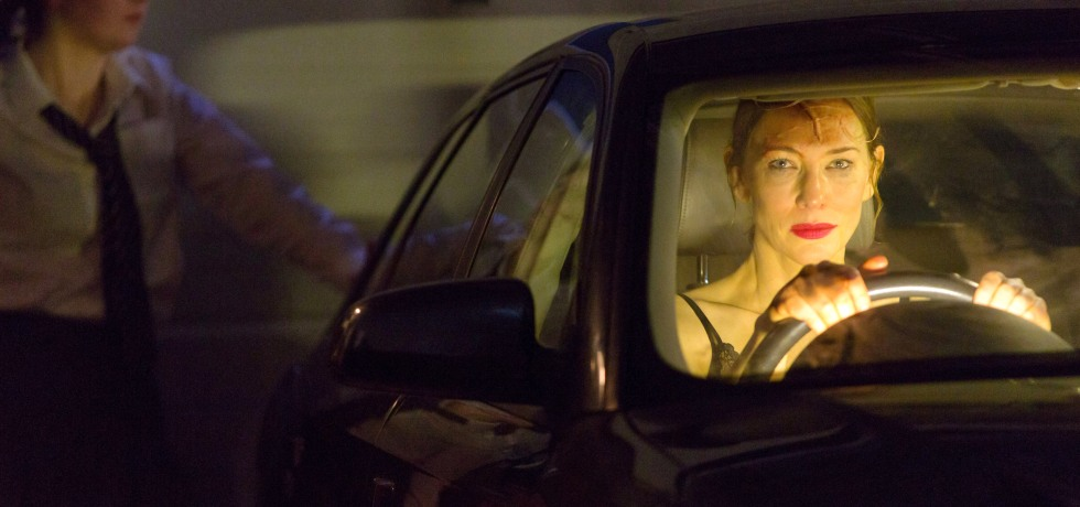 Cate Blanchett inside a black car in the driver's seat, wearing smudged makeup.