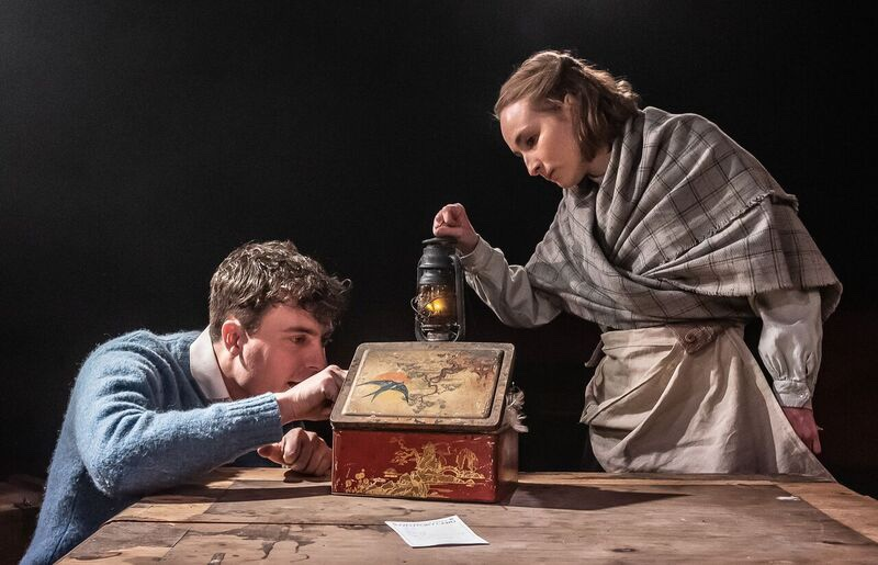 A box is open on a wooden desk. A man in a blue jumper on the left is kneeling down and looking inside it, while a woman is standing and peering inside while holding a lantern.