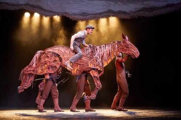Man riding a wooden puppet horse.