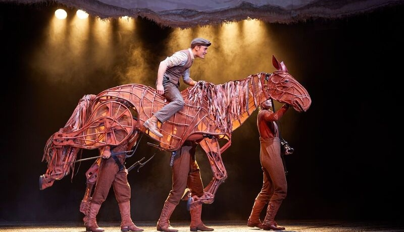 A man stands on a wooden horse puppet, which is manned by three people in brown costumes.
