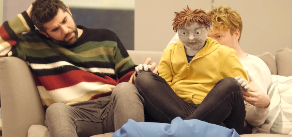A puppet wearing a yellow jacket and with light grey skin, manned by an actor in a white shirt behind him, sit on the sofa. To the left of him, a male actor in a striped jumper sits, with his right hand scratching his head.
