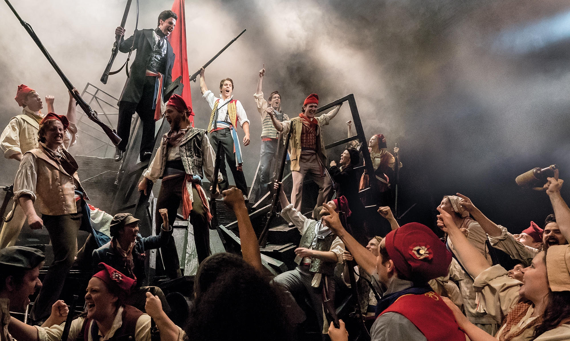 A group of French rebels from Les Mis gather around the barricades, raising their fists in solidarity.