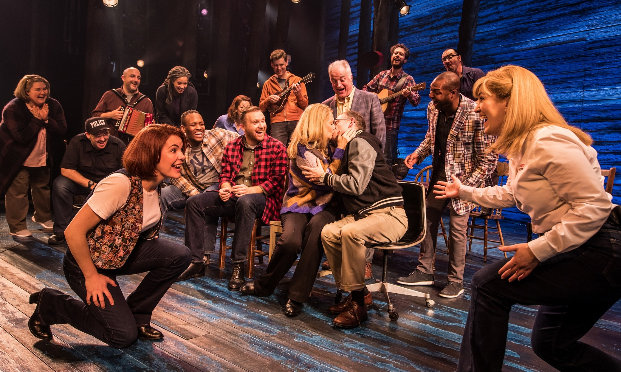 A group of friends gather around two people who are kissing each other, all of them with looks of happiness and surprise on their faces. A band is in the background. In the foreground, a woman is on one knee, smiling at another woman who leans forward on one knee, arms outstretched, smiling. They appear to be mid-dance.