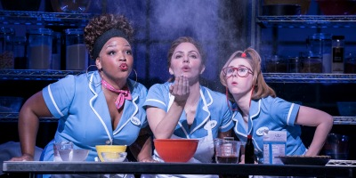 Three waitresses behind a kitchen desk.