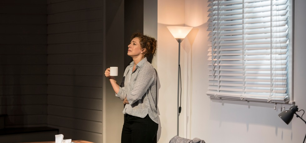 Alex Kingston holds a cup in her right hand, and rests against the wall. She is in an office, with a wooden table in front of her and white blinds in behind her.