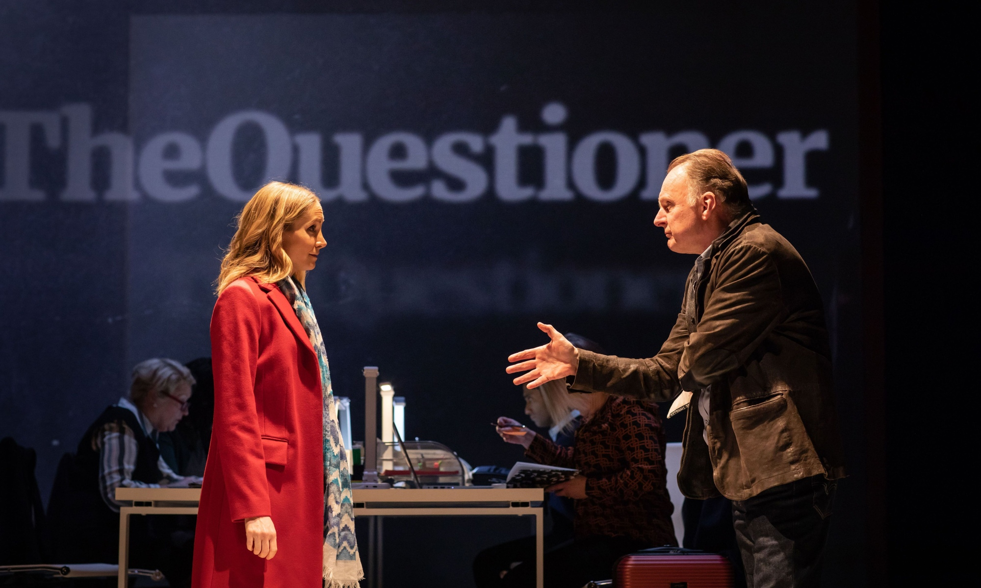 A woman on the left wearing a red coat and white and blue scarf. Her hair is blonde. On the right is a man in a brown coat, his right hand outstretched. People are working at a desk behind them, and the words 'The Questioner' is projected onto a wall, the font of which looks like the font for The Guardian.
