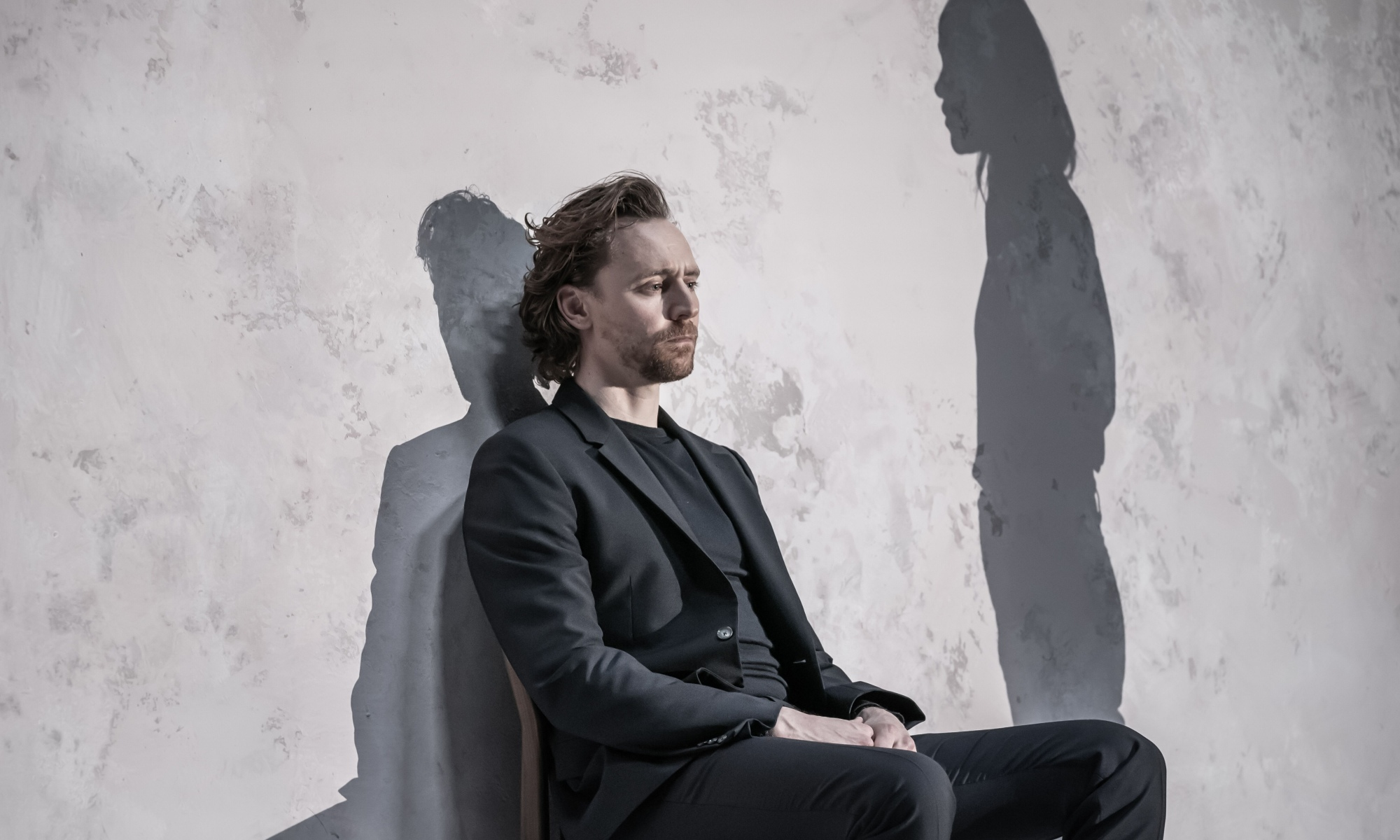 Tom Hiddleston has a neutral expression on his face as he sits on a chair against a stone wall. We can see his shadow, and to the right of this, the shadow of a woman.