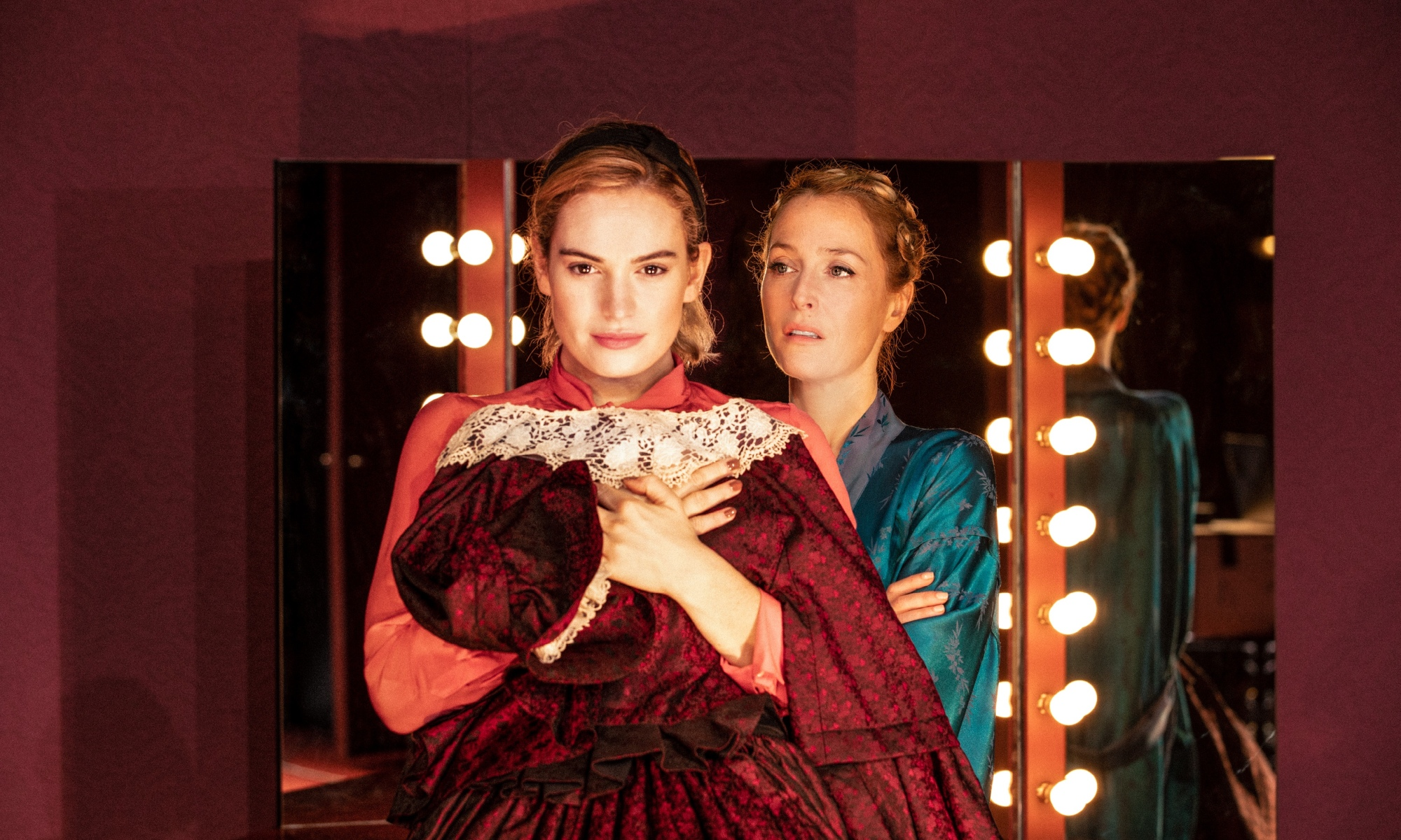 Lily James stands in front of three dressing room mirrors, holding a red dress close to her chest. Behind her, in a blue robe, looking at her, is Gillian Anderson.