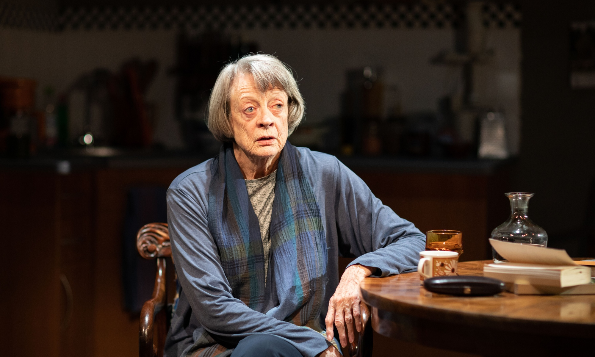 Maggie Smith wearing a blue shirt sits in a kitchen, at a wooden table with a glass of water and a book on it.