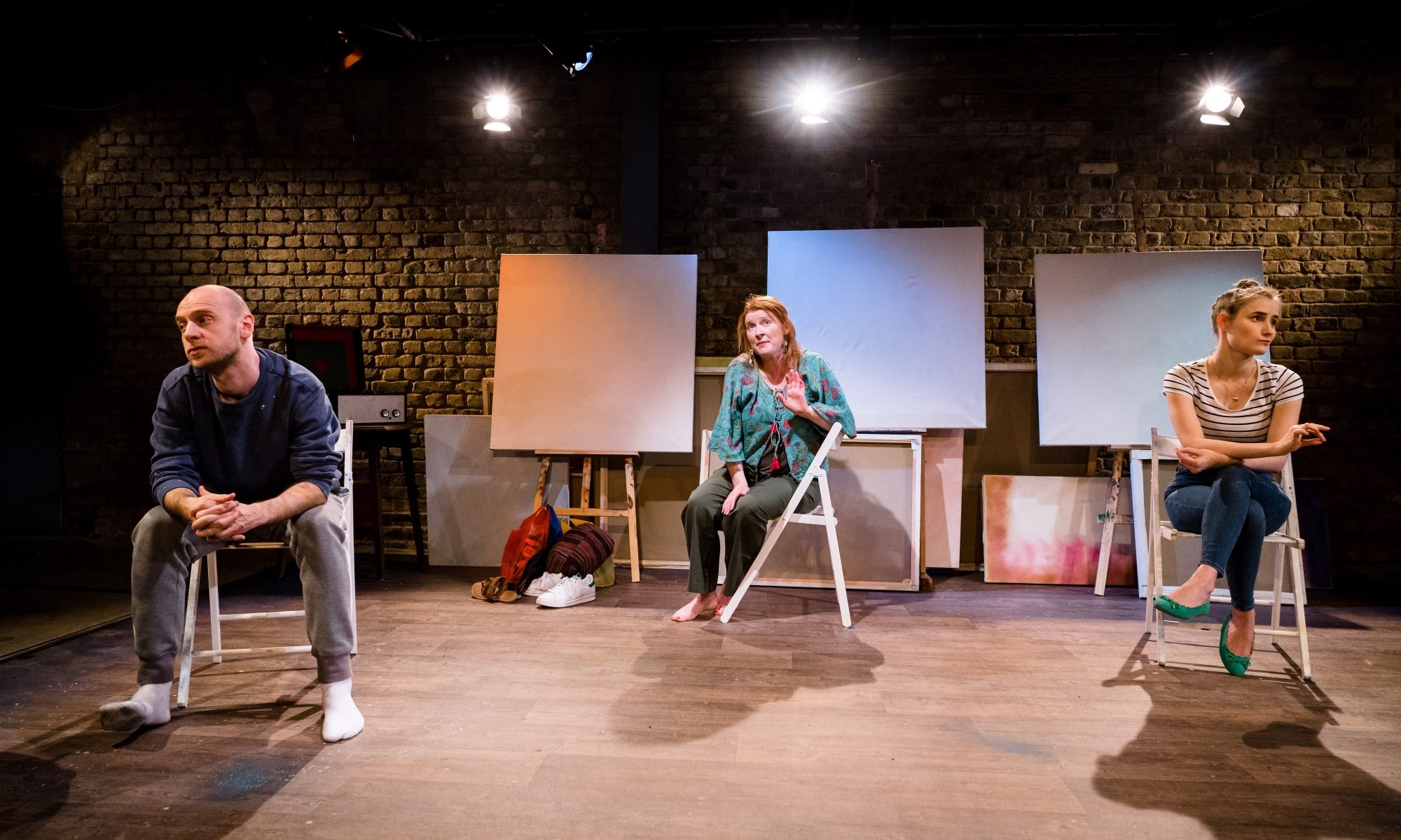 Three people (from left: a man, woman and younger woman) sit on white chairs in an arts studio. At the back of the room, mounted on easels, are three blank canvases.