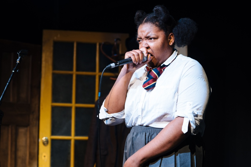 Young woman in school uniform speaking into microphone.