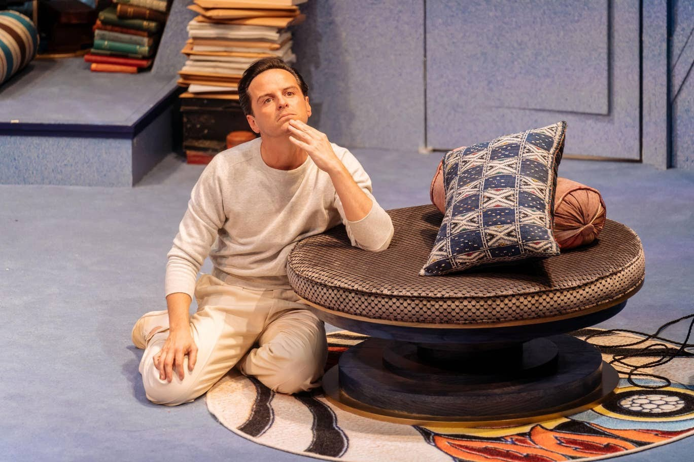 Andrew Scott, in all-white clothing, rests on a circular leather stool, which has two cushions on it.