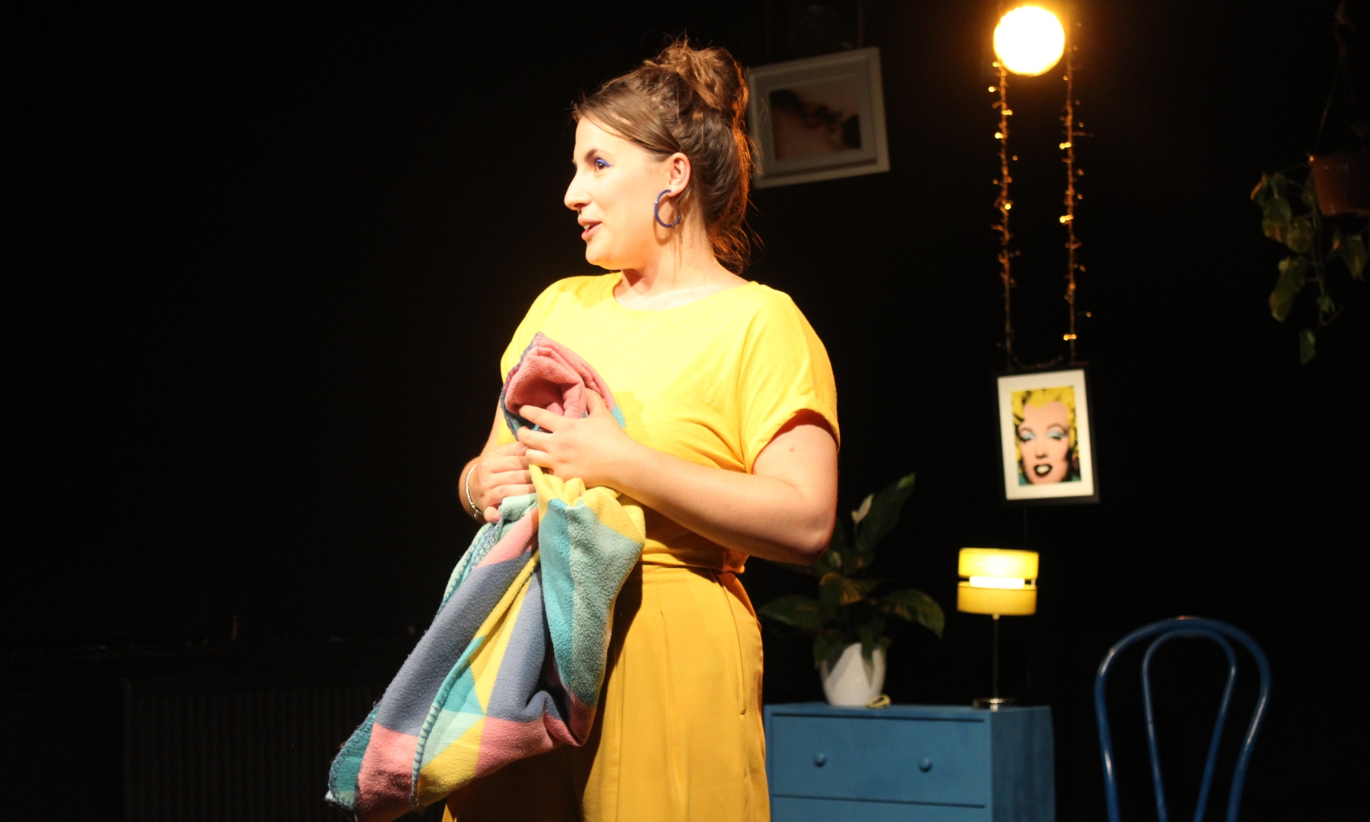 A woman in a yellow dress holds a multi-coloured scarf.