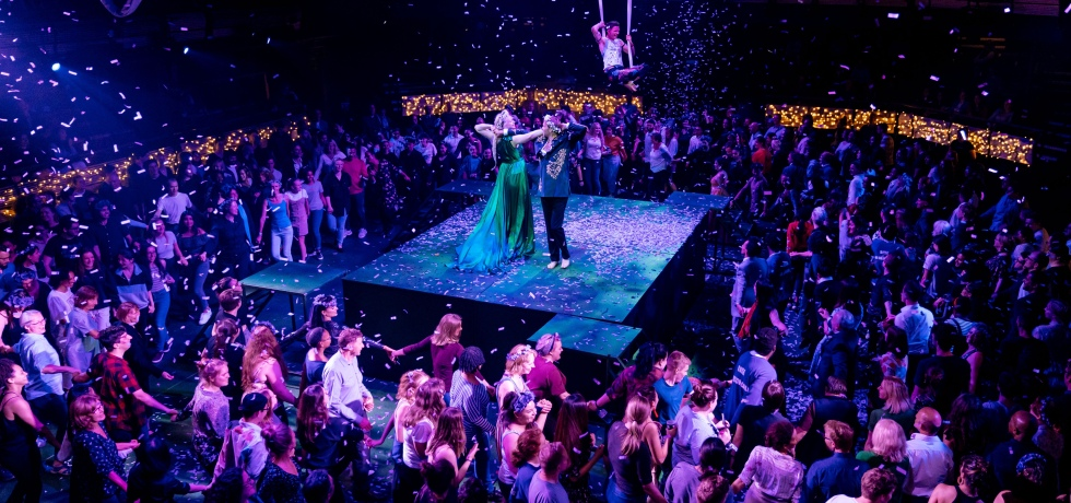 Audience members form rings around the central stage at the Bridge. The stage is a square, and shows a princess in a green dress, and a prince dancing together. A man in a vest also hangs from silk on the ceiling. Confetti also falls from the sky.