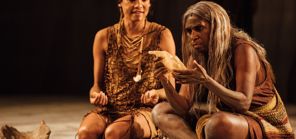 Two Aborigine women are sitting. The one on the right is reading a letter on parchment, which they hold in their hands.