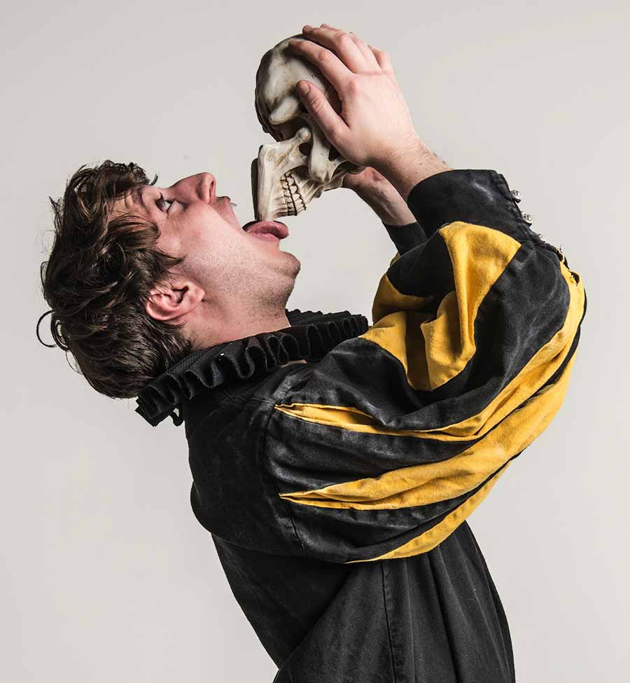 A man in Shakespearean dress holds a skull in both hands and licks the mouth edge of it with his tongue.