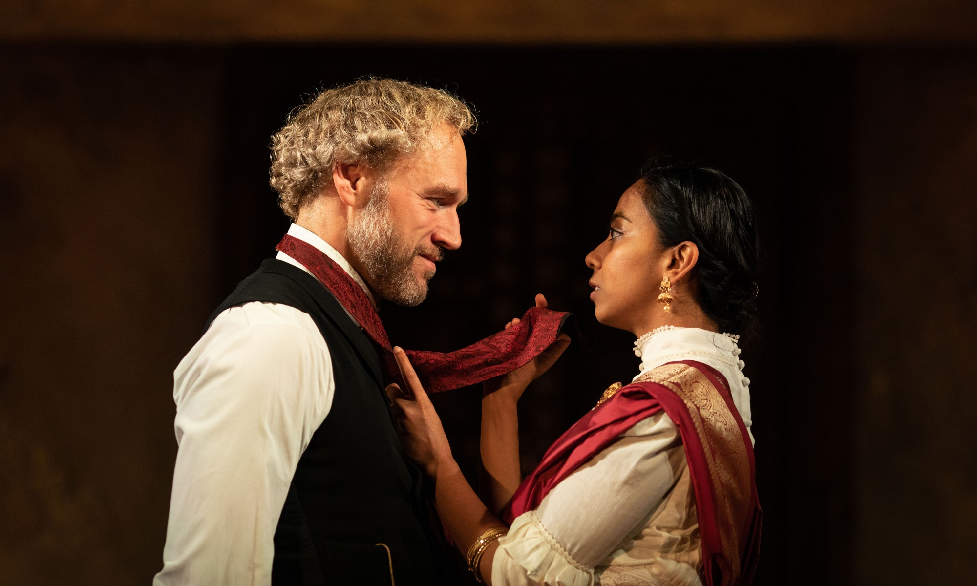 A suited man stares at a women, in Indian dress, who is holding his red tie.