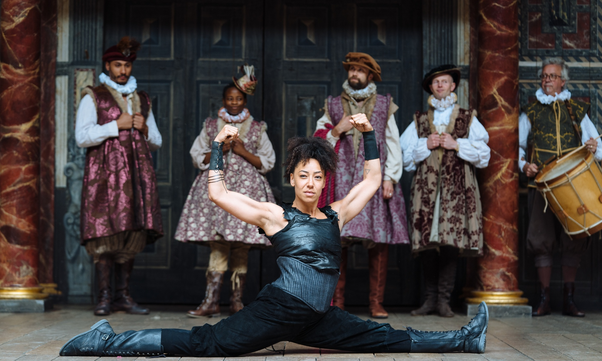 A women is doing the split whilst showing off her muscles. Behind them are five people (one of them holding a drum) in Shakespearean dress.
