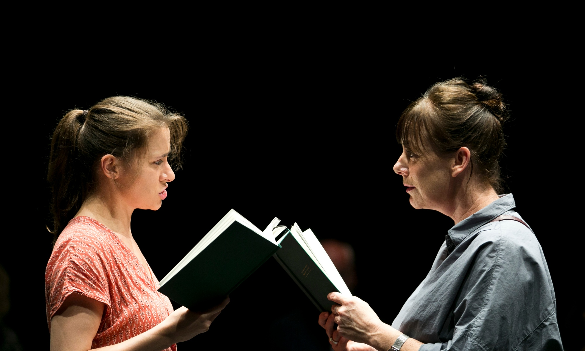 Two women look at each other, face-to-face, as they both read from green books in their hands.