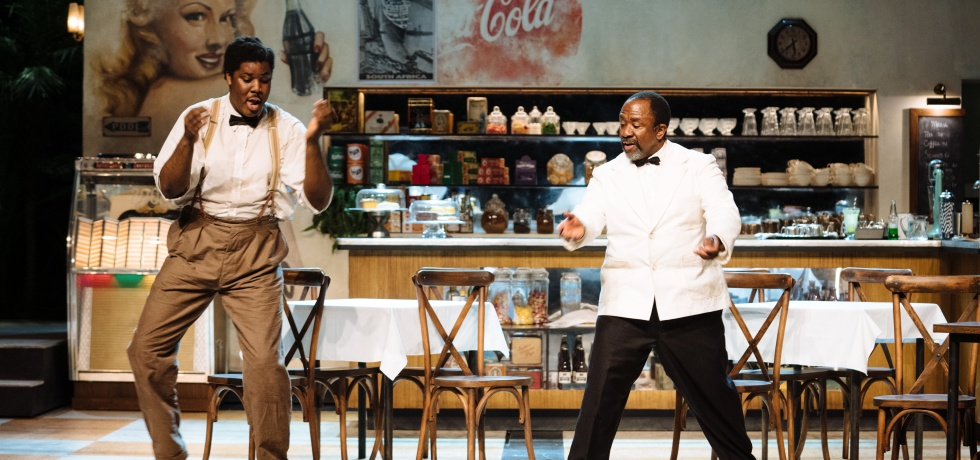 Two male waiters in a restaurant are dancing on stage.