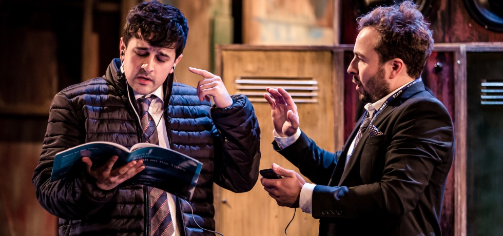 A boy on the left is wearing a puffer jacket and earphones, whilst reading from an open book. His left hand is pointing at his left ear. The teacher on the right is holding a phone connected to the earphones in his left hand, and is talking to the boy.