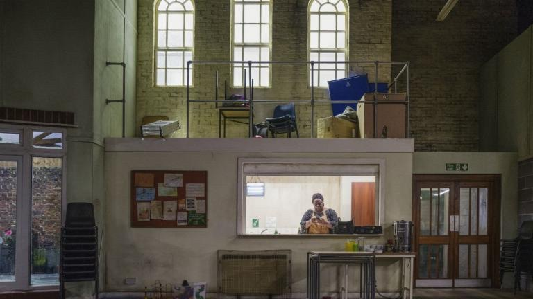 A community centre. In the background, through a window in a wall to the kitchen, a woman is looking at her phone.