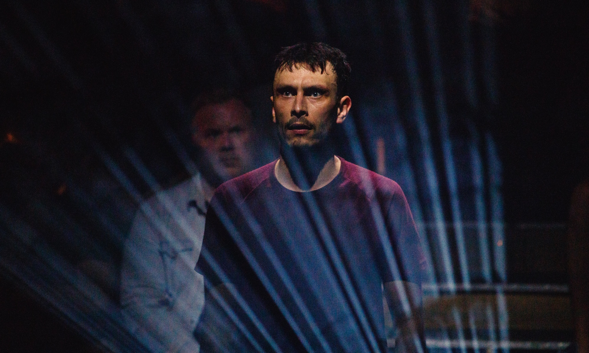 A man in a red shirt stares into the distance, with a look of fear about him. His face is lit up with a blue light from below him.