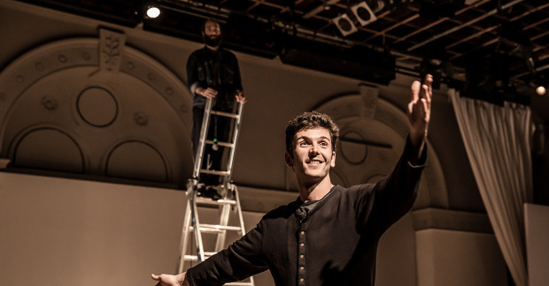 A man has his left arm outstretched, smiling. Behind him is a man standing at the top of a ladder.