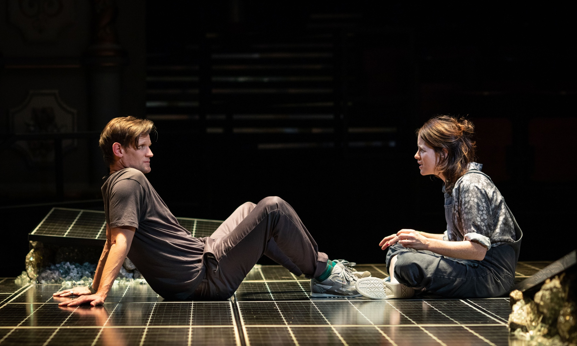 Matt Smith (left) and Clare Foy (right) sit on stage facing each other. The floor of the set has a solar panel-like, striped design.