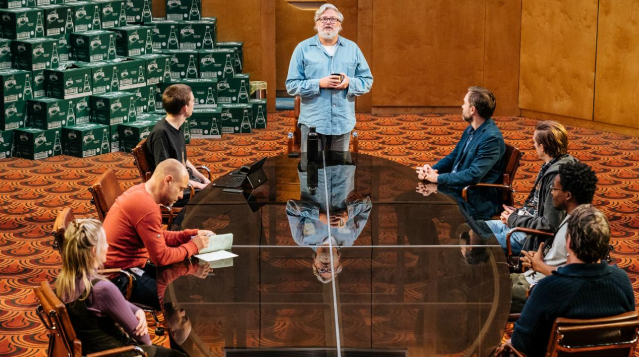 Eight people are gathered around a round table. All but one, who is writing in a book, is looking at someone at the head of the table, who is standing.