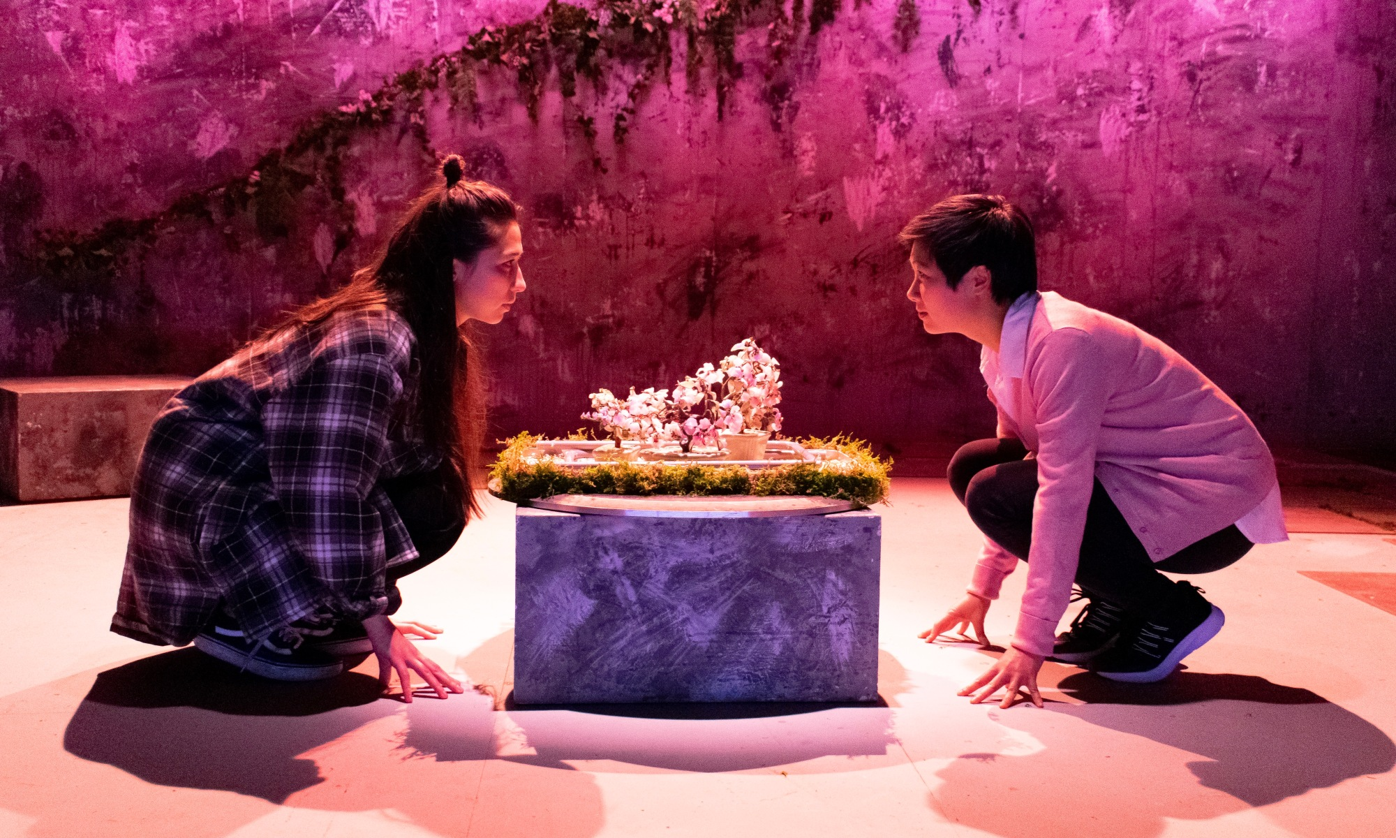 Two women crouch either side of a stone table, which has a pink flower and grass on top of it.