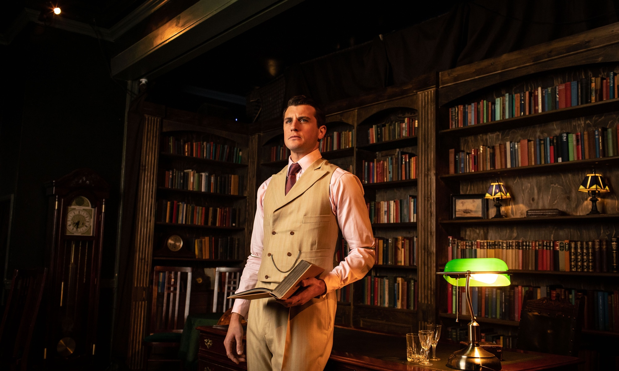 A man in a cream waistcoat holds an open book in his left hand. He is in an office, with several bookshelves behind him.