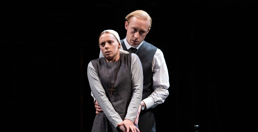 A nun in grey clothing has a scared expression and has her hands clasped together. A man in a waistcoat with combed blonde hair holds her waist from behind.