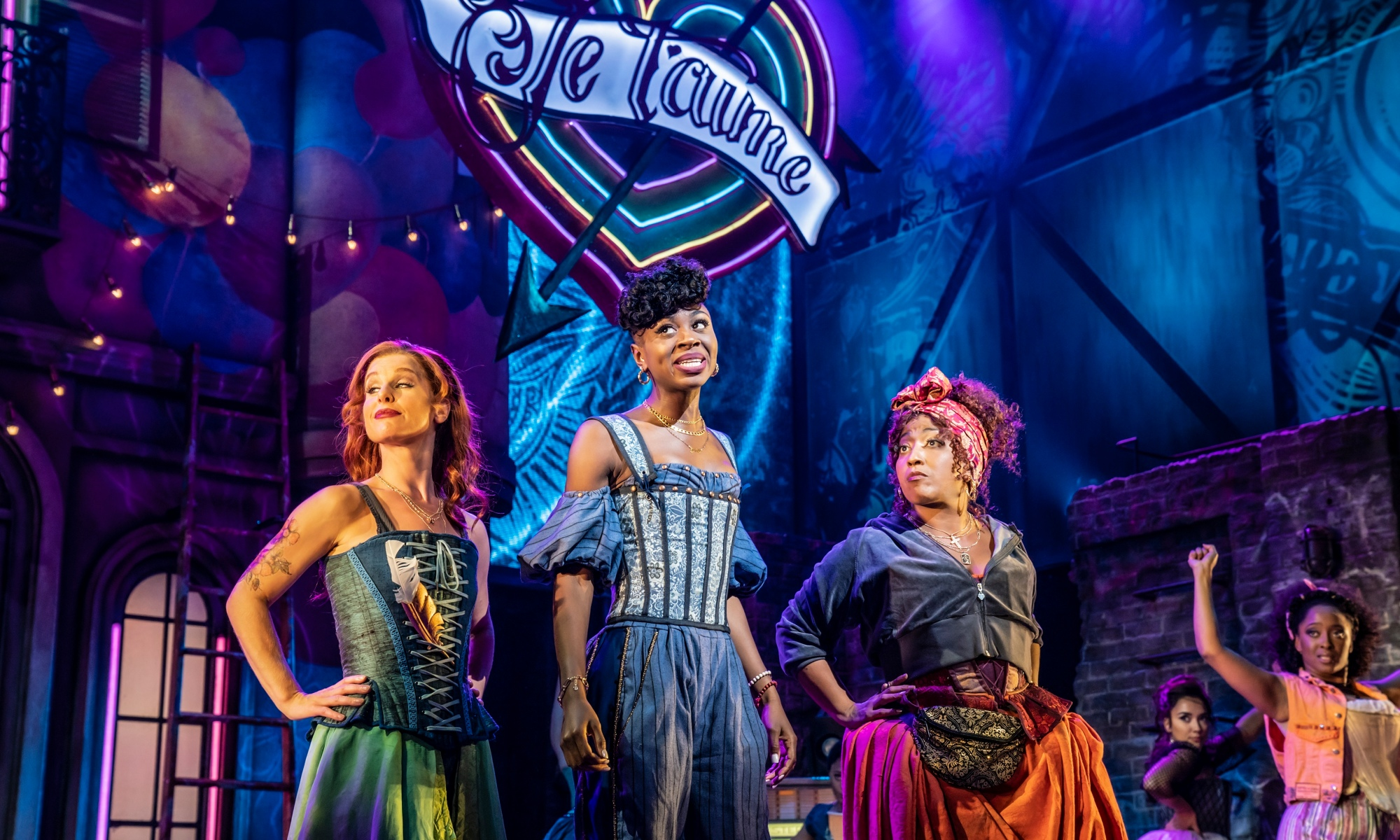 Three women in Shakespearean dress, in bright colours, look at someone to the right of them off-camera. A neon sign of a love heart is in the air with the words 'Je t'aime' inside it.