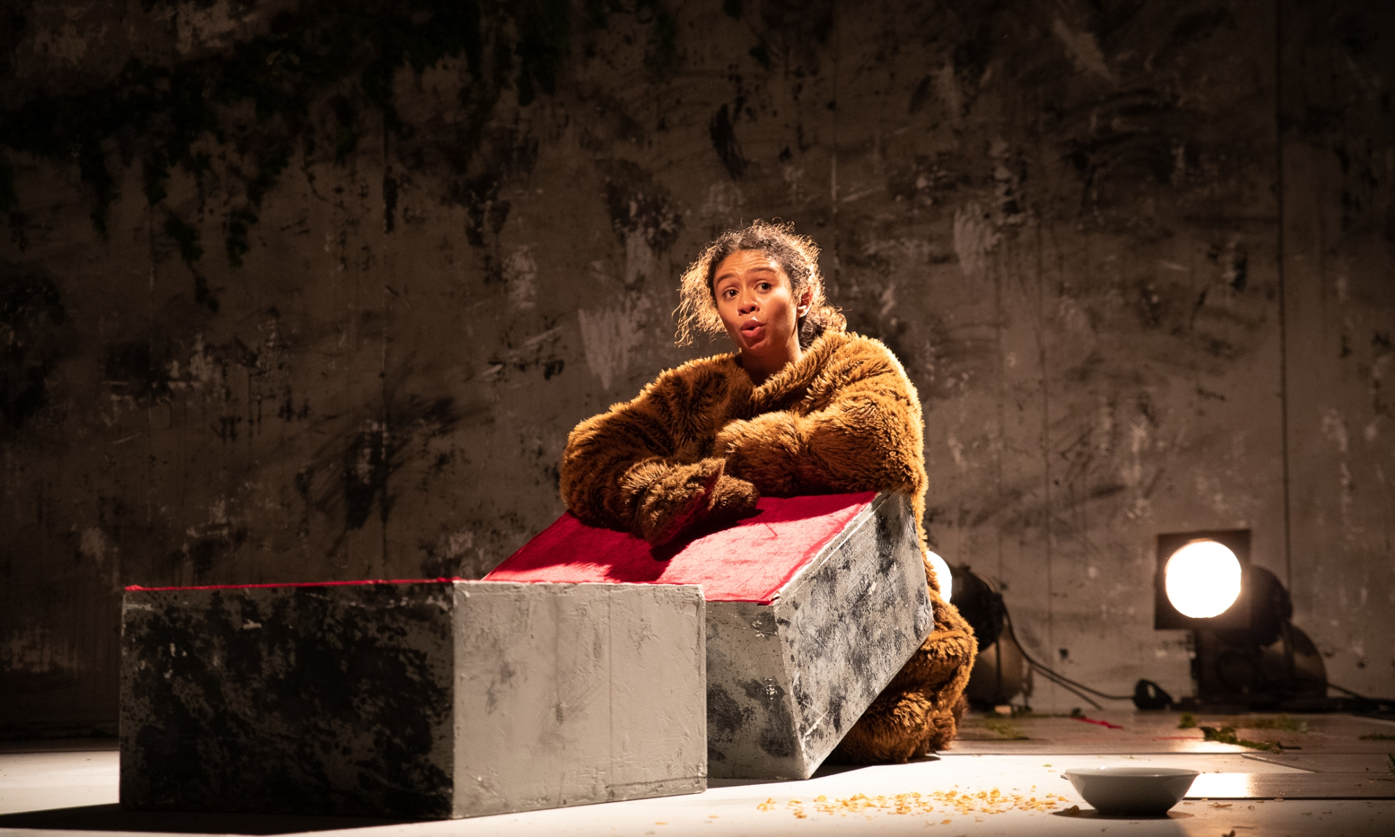 A women in a bear costume (except for the head) rest her hands on a stone block. Another stone block is in front of this one. To the left on the floor is a bowl of cereal, with several flakes on the floor next to the bowl.