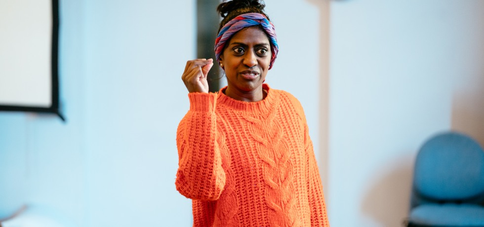 Actress Nadia Nadarajah, wearing a pink headscarf and orange jumper. She is in a rehearsal room.