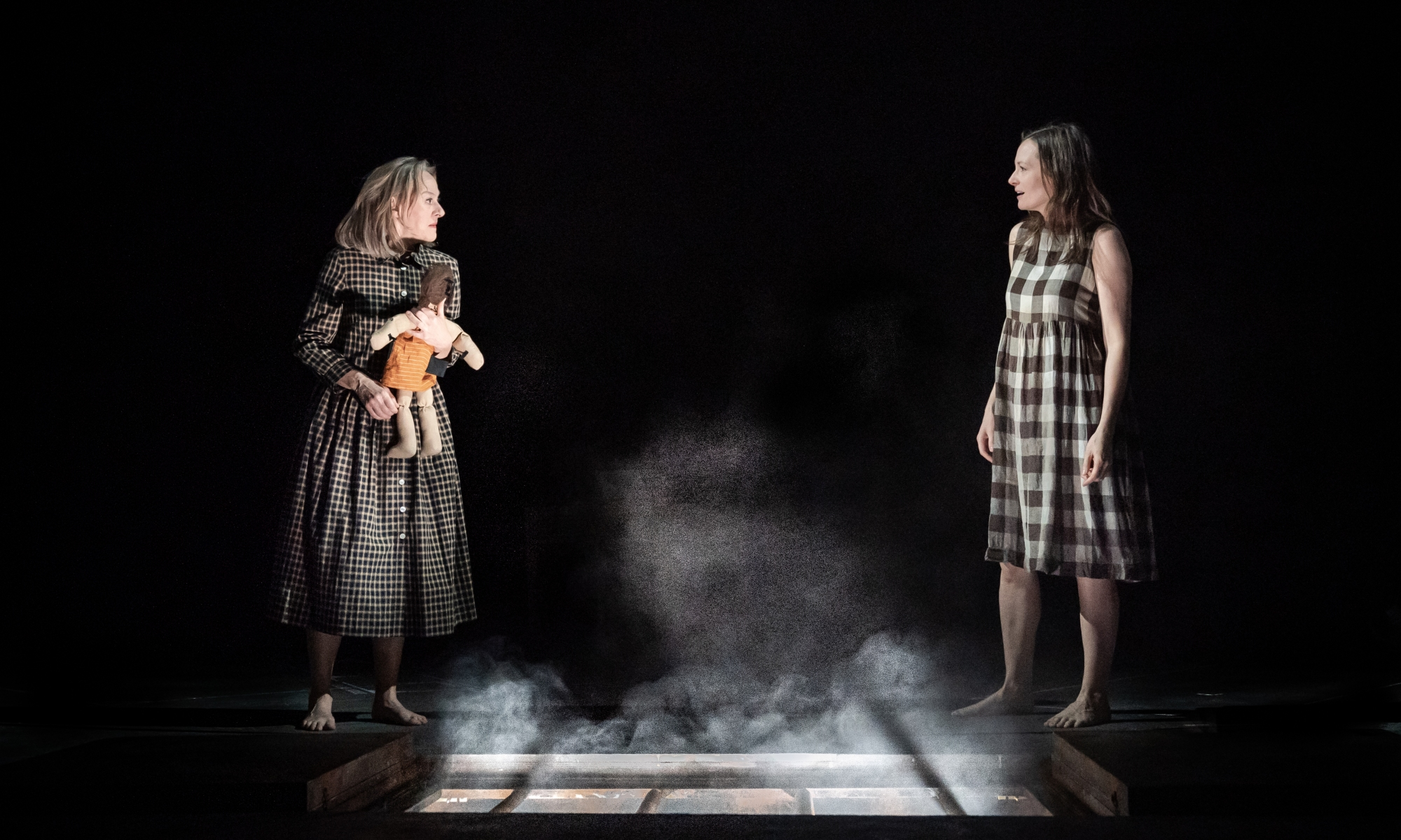 A woman on the left holds a toy doll and wears a black dress. On the right, another woman in a check dress. In between them on the floor is a window which emits a white light.