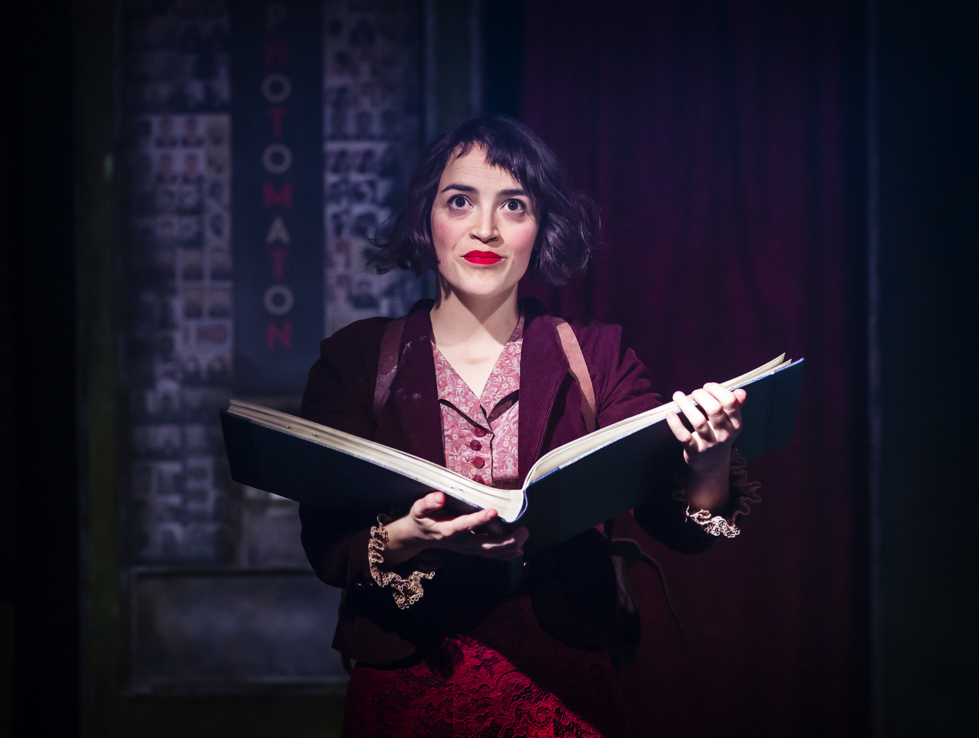 Amelie, with curly black hair and red lipstick, in red clothes, smiles as he holds and open book.