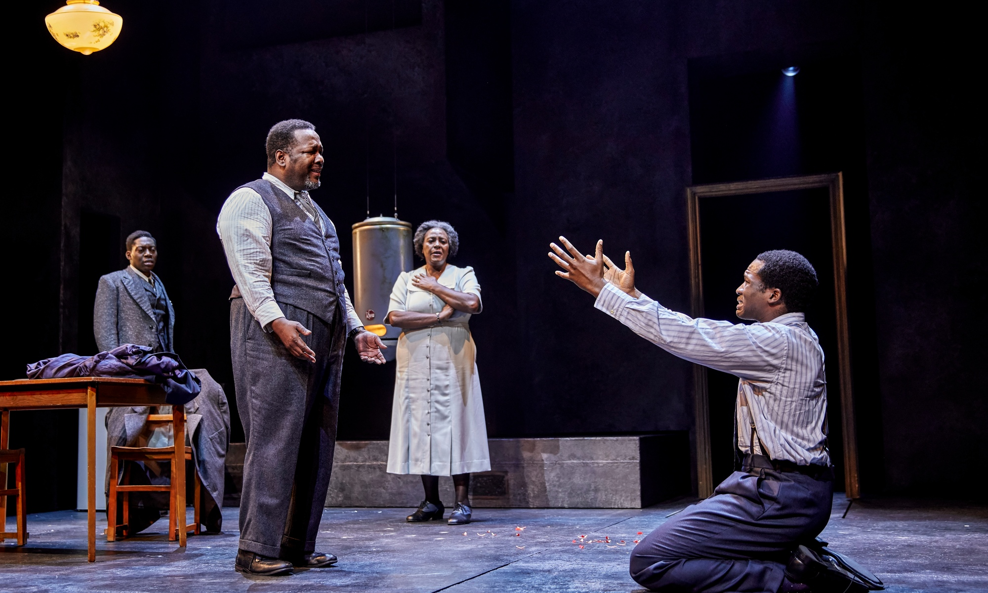 A man to the left of the stage has his arms slightly in front of them, with their palms upwards. On the floor on the right, with his arms outstretched, is a man (his son), who appears emotional. Another brother and the mother are both watching on in the background.